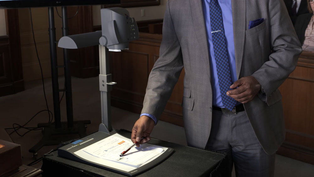 Image of a man pointing to a document on an overhead projector